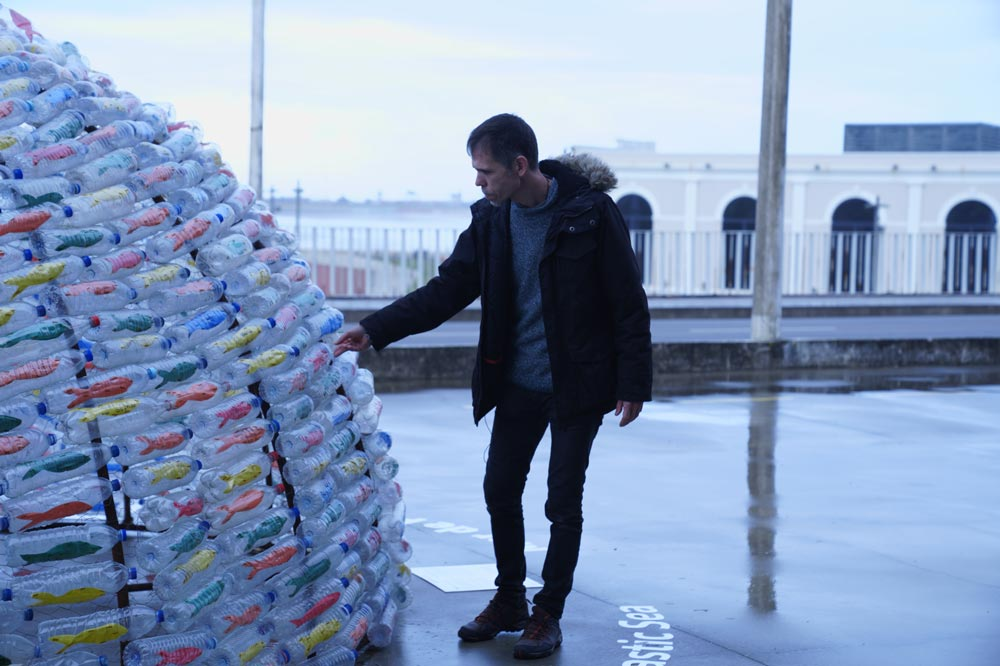 Man with a pyramid of bottle